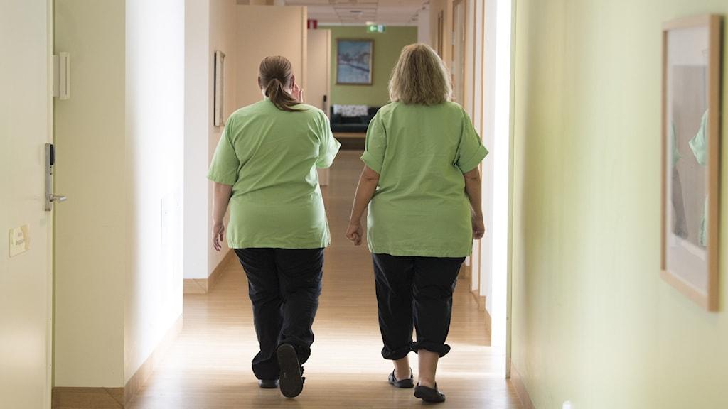 Två undersköterskor på ett äldreboende går i en korridor