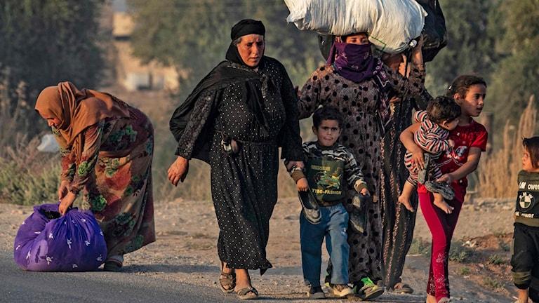 Folk flyr från flygräder i nordöstra Syrien.