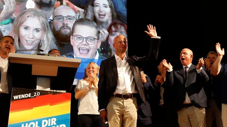 AfD:s partiledaren i Brandenburg, Andreas Kalbitz vinkar på scenen efter att de första vallokalsundersökningarna offentliggjorts.