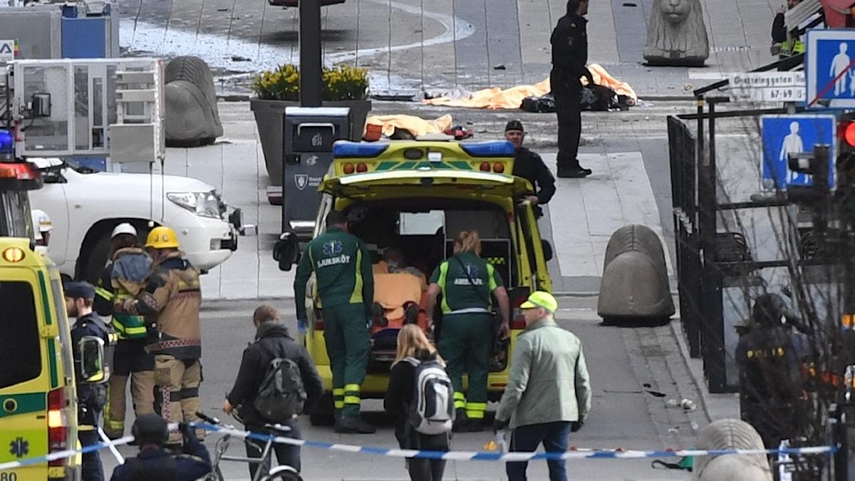 Ambulanspersonal hjälper skadade efter terrordådet på Drottninggatan.
