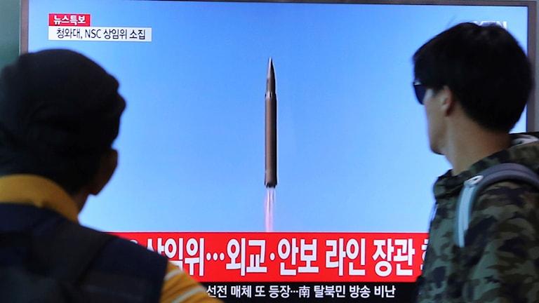 Människor tittar på TV-bilder av Nordkoreas robottest i augusti 2017 (arkivbild). Foto: Ahn Young-joon/TT.