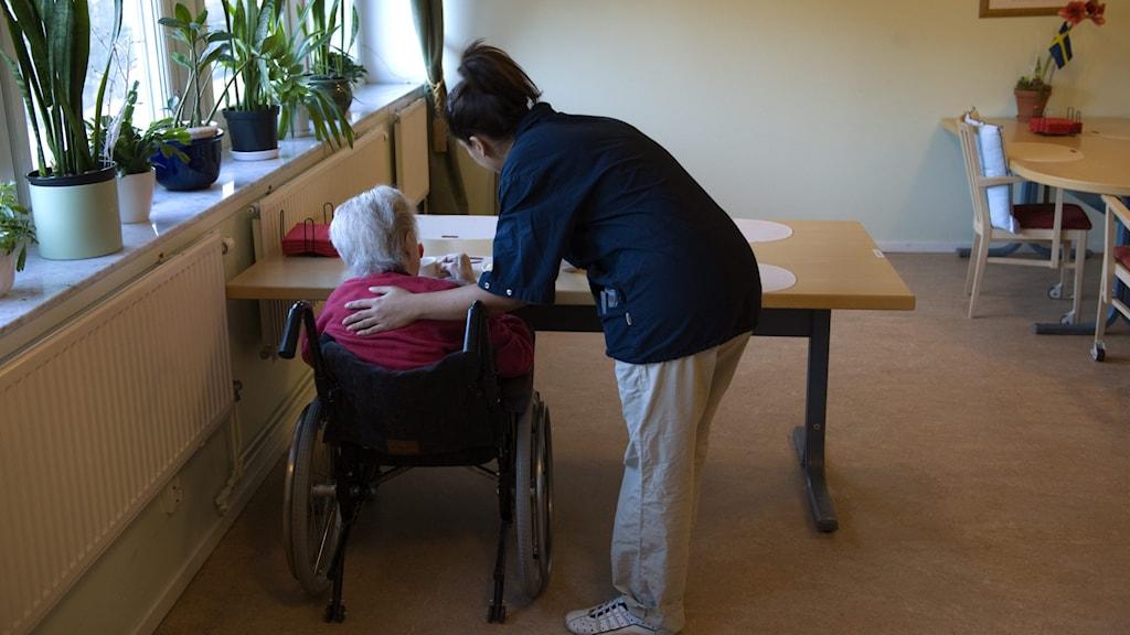 Undersköterska hjälper äldre kvinna på äldreboende i Stockholm