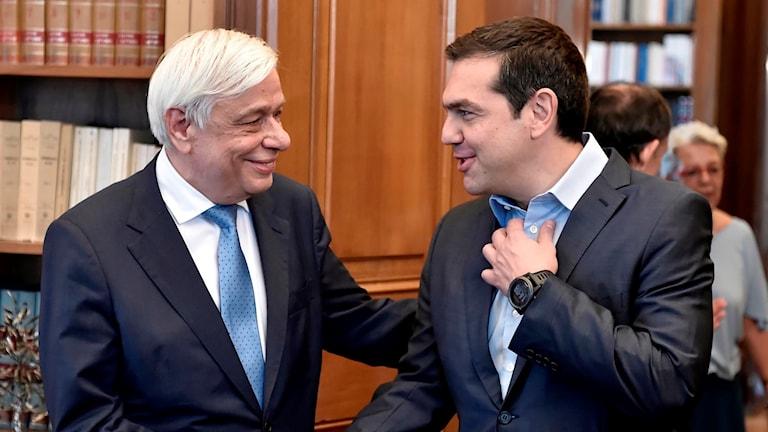 Den grekiska presidenten Prokopis Pavlopoulos skakar hand med den grekiske premiärministern Alexis Tsipras.