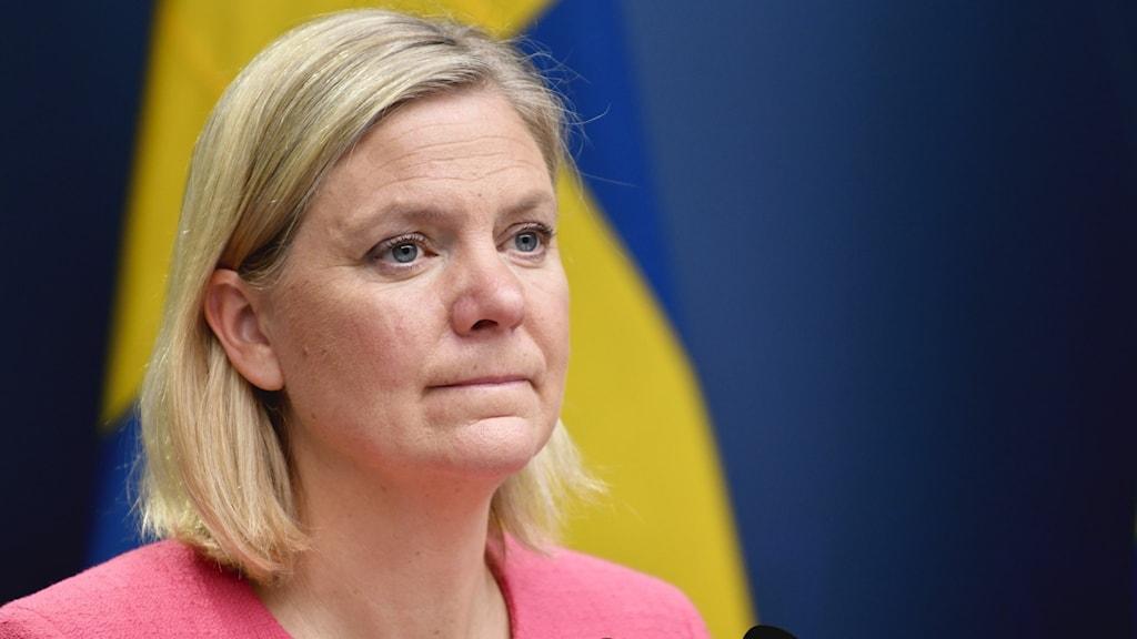 Finansminister framför en sverigeflagga.