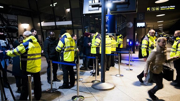 Bilden visar passagerare som passerar ID-kontrollerna på tågperrongen under Köpenhamns flygplats. Säkerhetspersonal i neongula jackor kontrollera id-handlingar. Foto: Emil Langvad/TT.