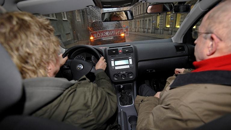 Bild tagen från baksätet på en bil, framåt. Bakifrån syns chaufför och passagerare i bilens framsäten.