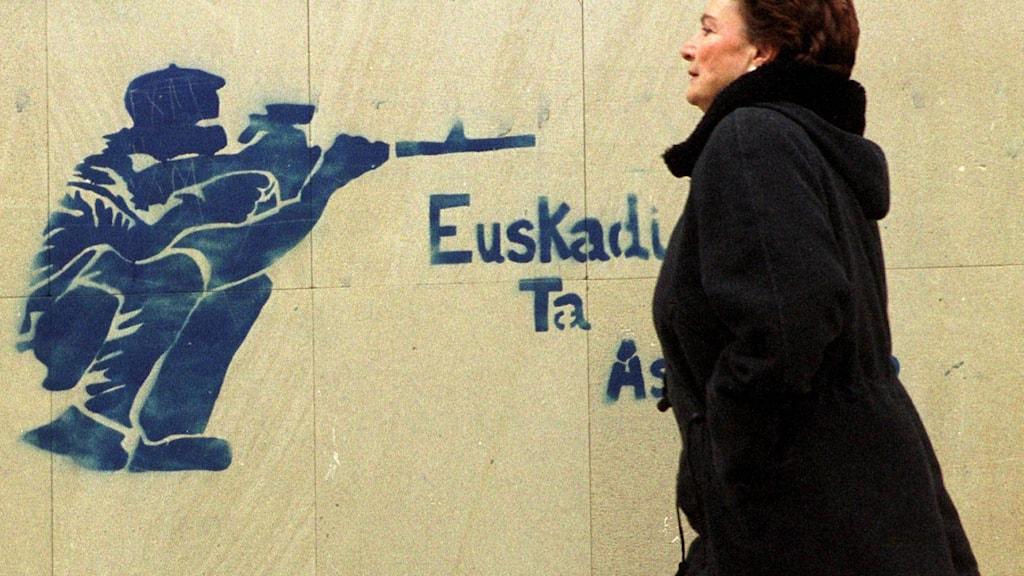 En kvinna passerar en affisch med ETA-symbolik i norra Spanien 1999. Foto: TT.