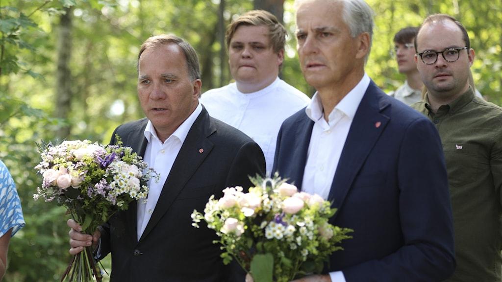 Två män håller i blomsterbuketter.