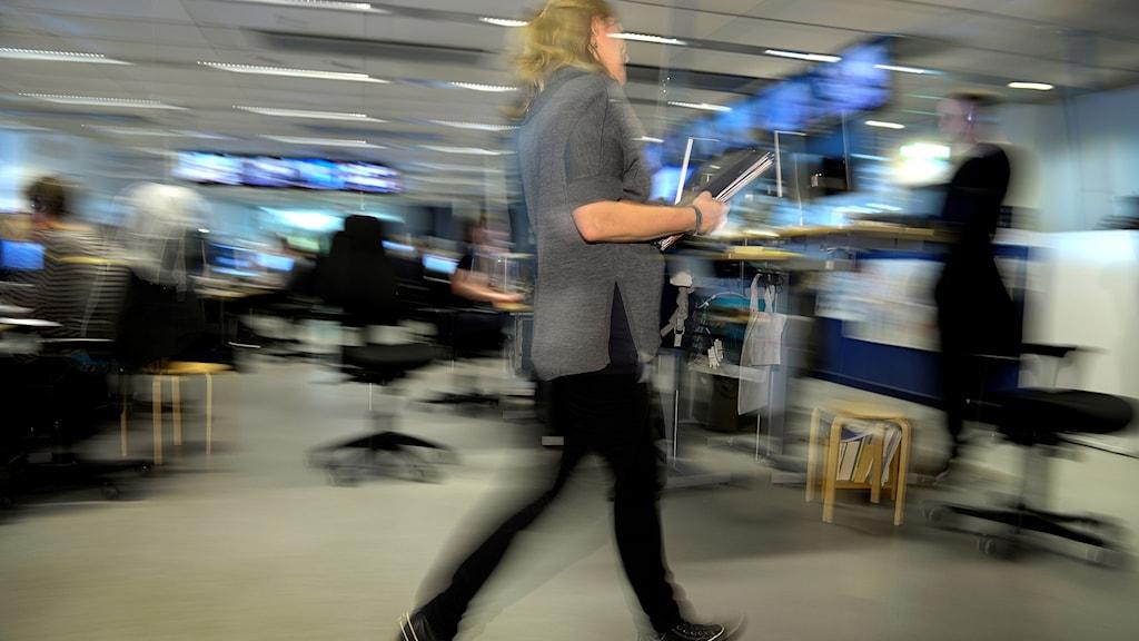 En kvinna  går i rask takt på kontor