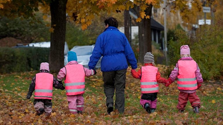 Dagisfröken med barn på promenad.