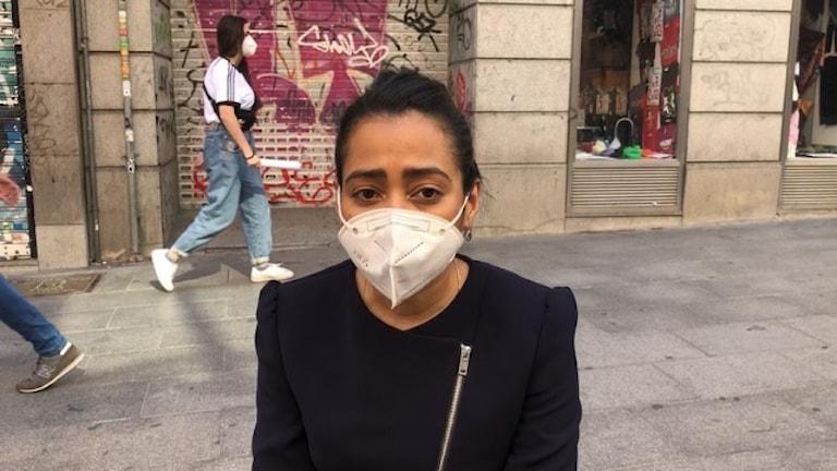 Kvinna med munskydd på gata i Spanien.