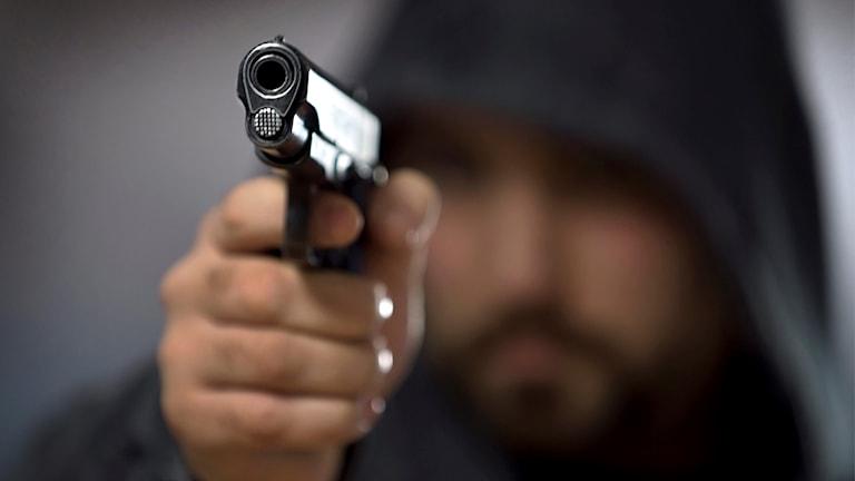 Oskarp man som riktar pistol mot kameran.