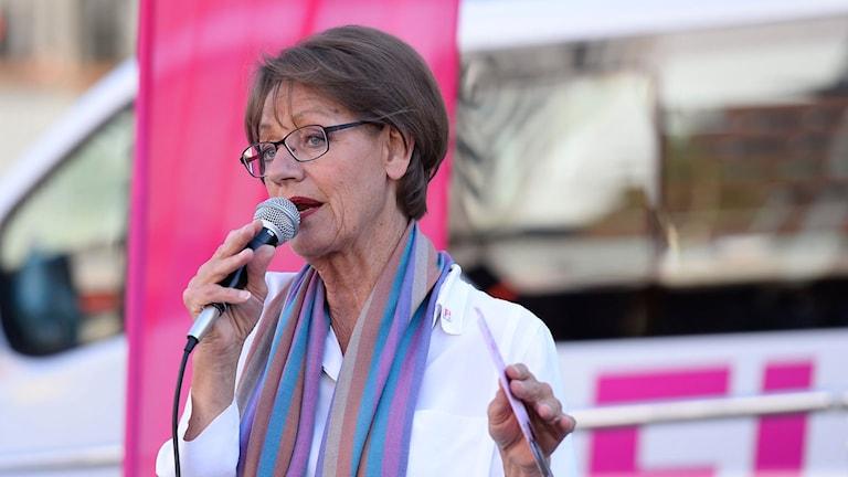 Gudrun Schyman under ett tal framför en bil med FI:s logga.