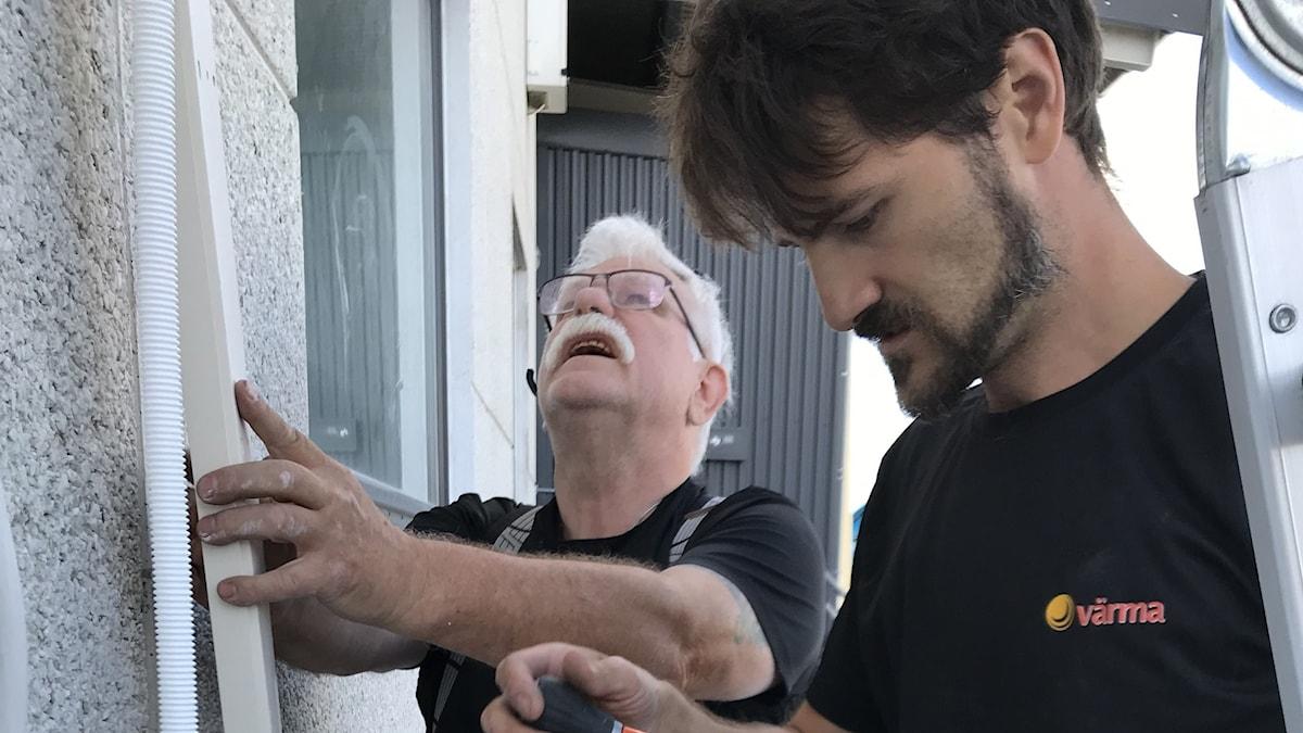 Montören Eric Johansson och kylteknikern David Bergqvist monterar en luftvärmepump/AC på en fasad.