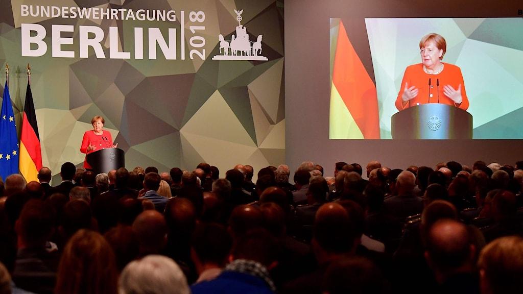 Kvinna talar inför publik.