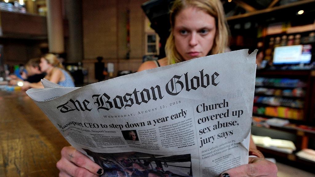 Kvinna som läser The Boston Globe