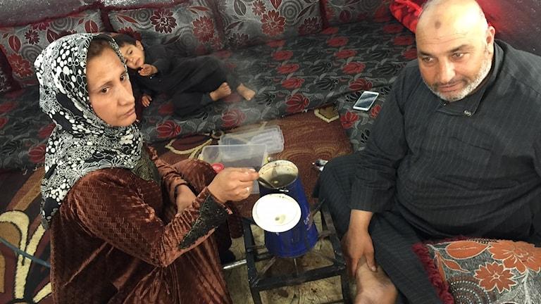 Ahmed Hammoud, 52, från Aleppo gör kaffe på golvet i flyktingtältet. Hans fru Dalal serverar kaffet.