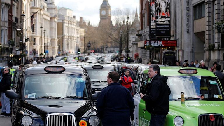 Taxichaufförer i London blockerar en gata i protest mot digitala tjänster som Uber.
