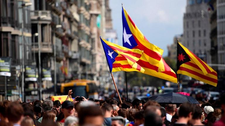 Människor på Barcelonas gator med Kataloniens flagga.