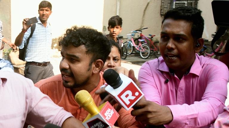 Journalister frågar ut en anklagad man utanför hans hem.