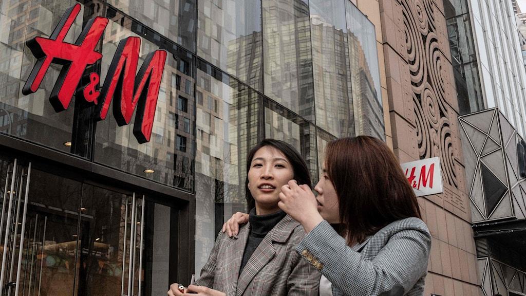 Två kvinnor går förbi ett H&M i Peking.