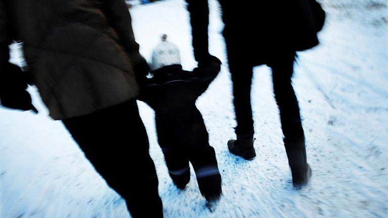 Barn i vinteroverall är ute och går med sina föräldrar.