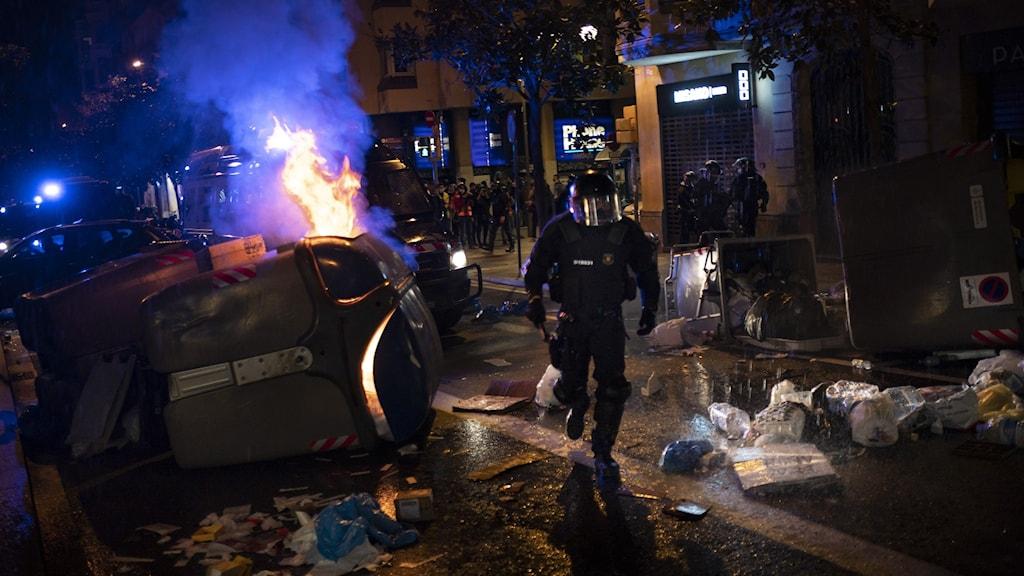 Polis i utrustning springer, bil brinner på mörk gata.