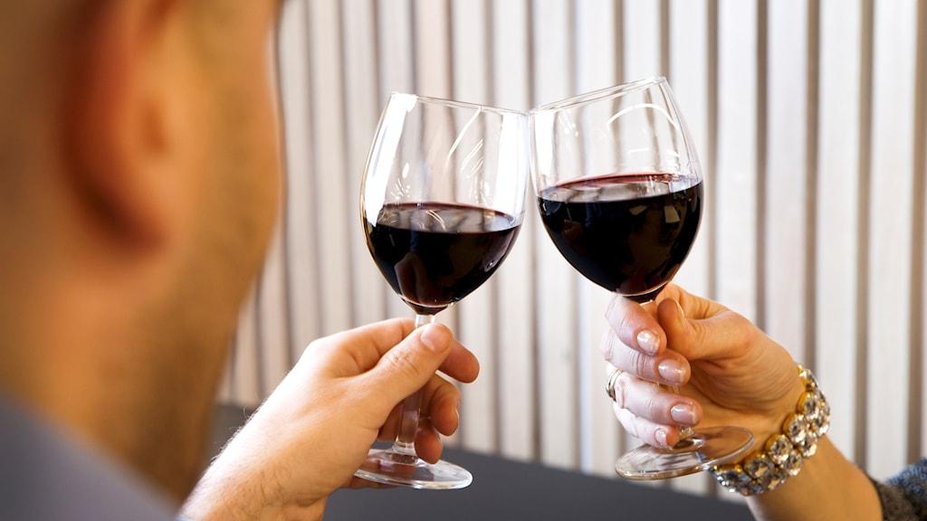 Två händer skålar med varsitt glas rött vin.