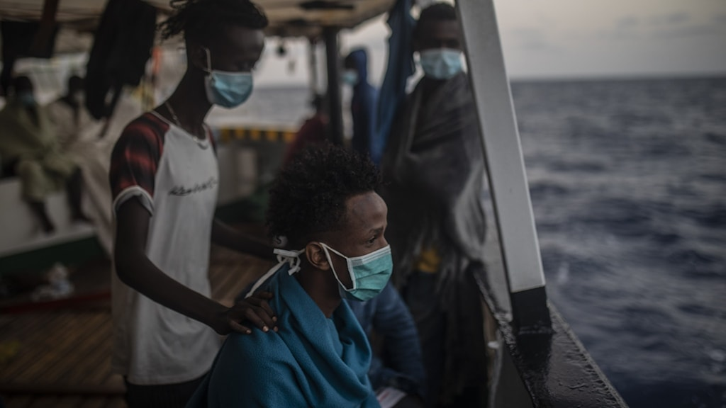 Två mörkhyade migranter med munskydd på en båt, tittar ut över havet.