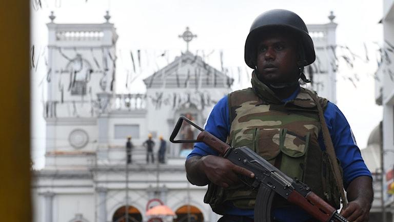 Lankesisk soldat står på vakt utanför en katolsk kyrka.