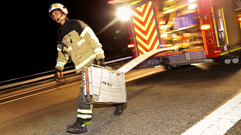 Brandman som rullar ut slang från en brandbil.
