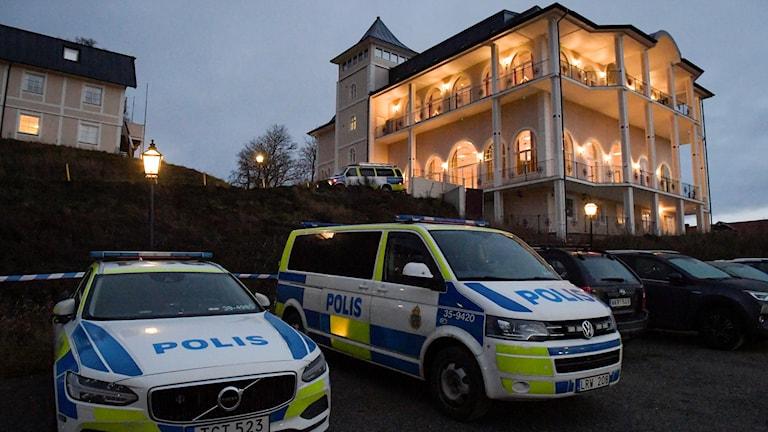 Polisbilar uppställda framför slottsbyggnad
