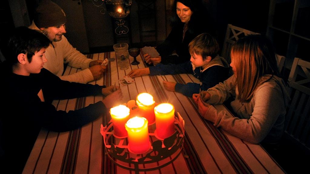 En familj som sitter runt ett köksbord med tända stearinljus