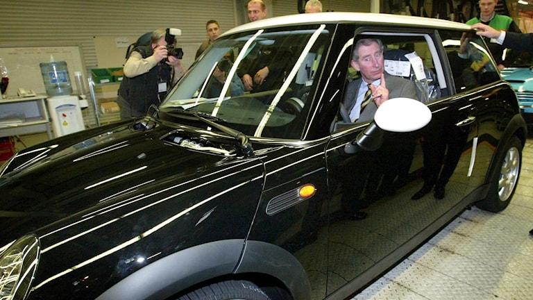 Storbritanniens prince Charles i den typiskt brittiska bilen Mini, vars tillverkning kan flyttas från Storbritannien vid en hård brexit.
