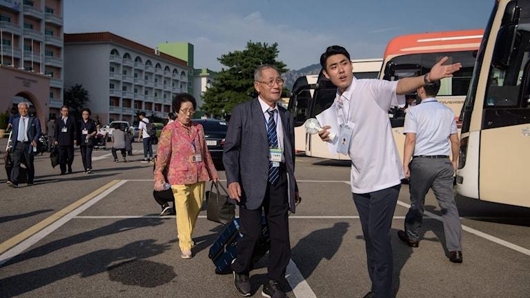 En koreansk äldre man och kvinna blir visade till en buss.