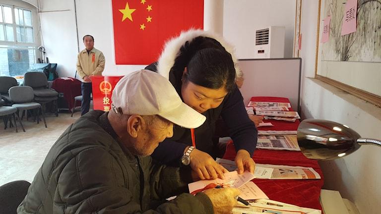 En 94-årig Pekingbo får hjälp av en volontär att lägga sin röst i valet till den lokala folkkongressen, som sedan väljer högre nivåer av representanter och ledare. Foto: Hanna Sahlberg/SR.