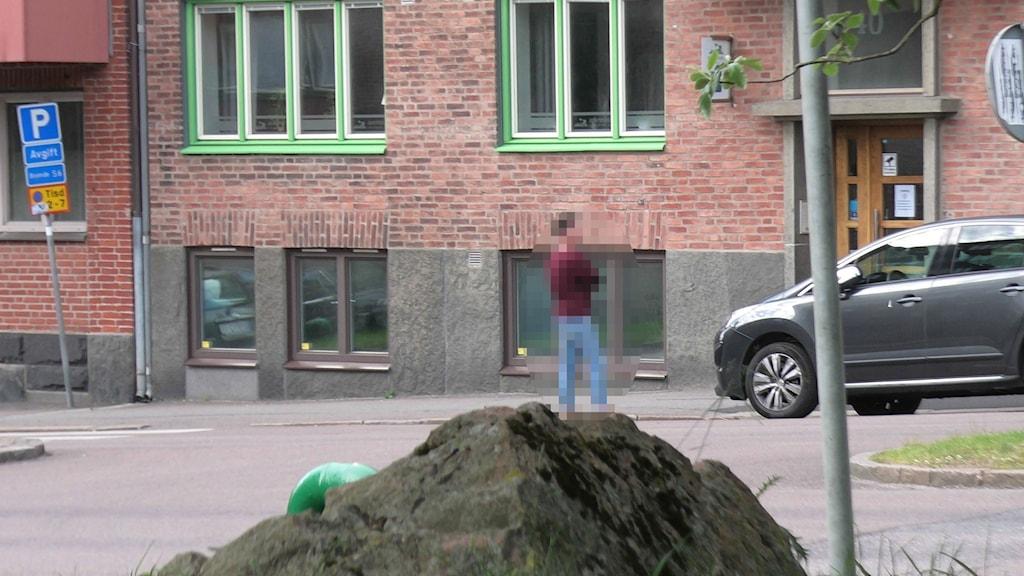 En man står utanför en byggnad.