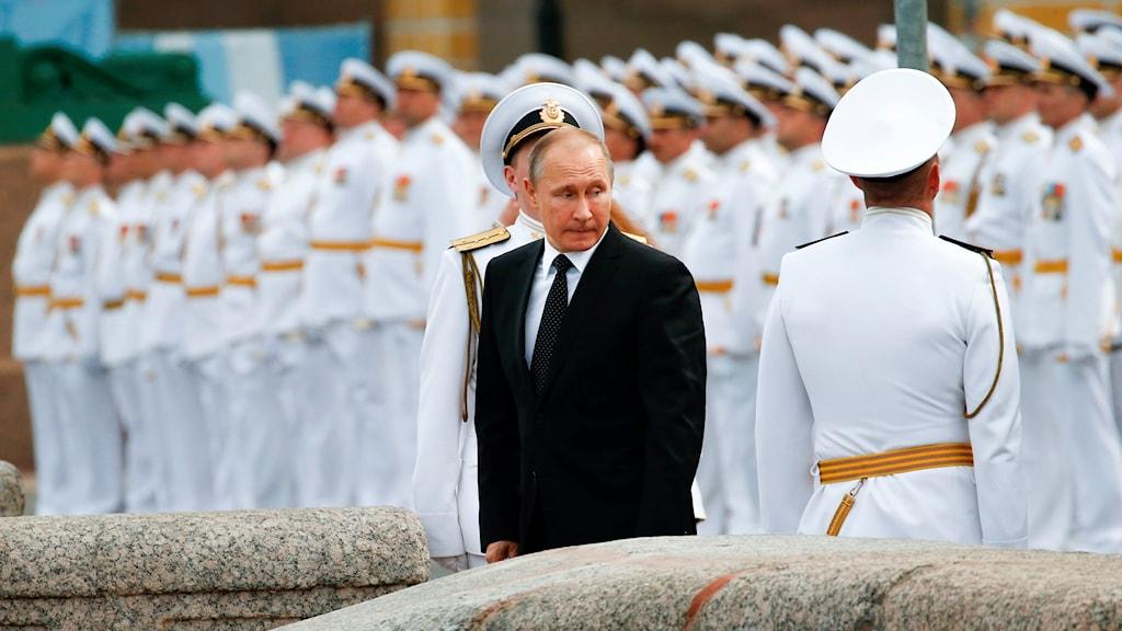 Kostymklädd man framför soldater i flottans uniform.