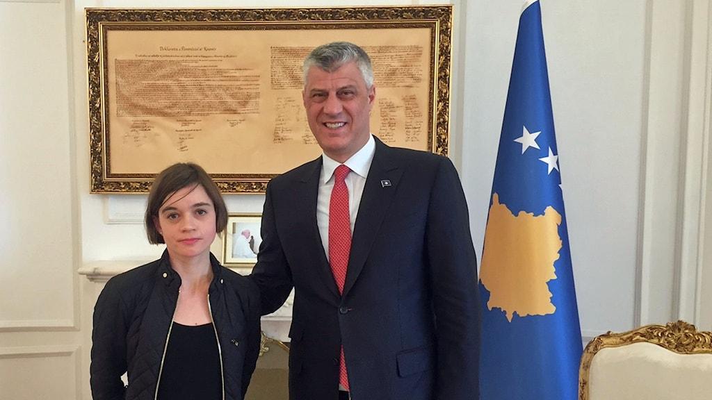 Kvinna och man framför ett gammalt dokument och Kosovos flagga bredvid.
