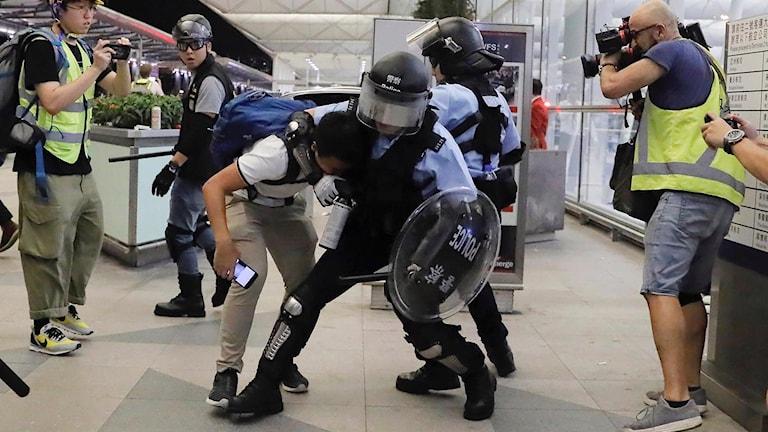 Polis drabbar samman med demonstranter vid Hongkongs flygplats under tisdagskvällen.