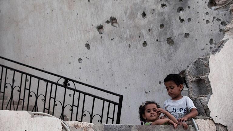 Arkivfoto på två barn utanför ett hus täckt med kulhål.