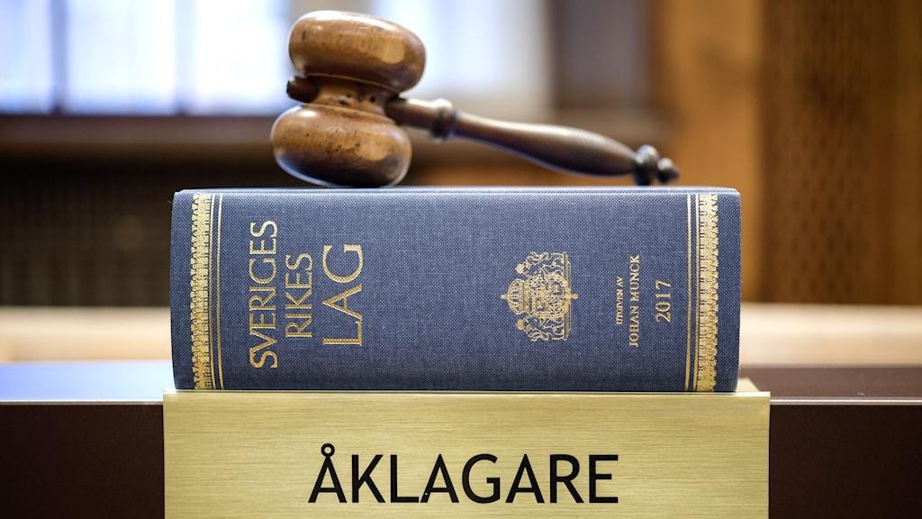 """En domargavel, en upplaga av boken Sveriges rikes lag med guldtext och blått omslag och en skylt i mässing där det står """"åklagare"""" står i en domstolslokal. Foto: Anders Wiklund/TT"""