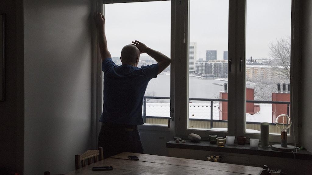 En man tittar ut genom fönstret i sin lägenhet. Genrebild.