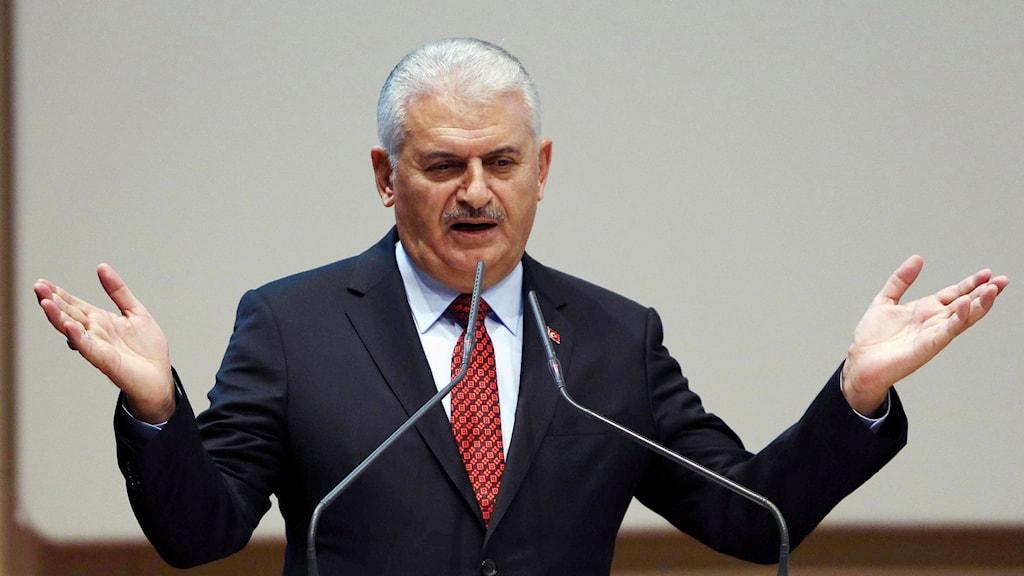 Turkiets premiärminister pratar vid ett podium och har båda händerna i luften