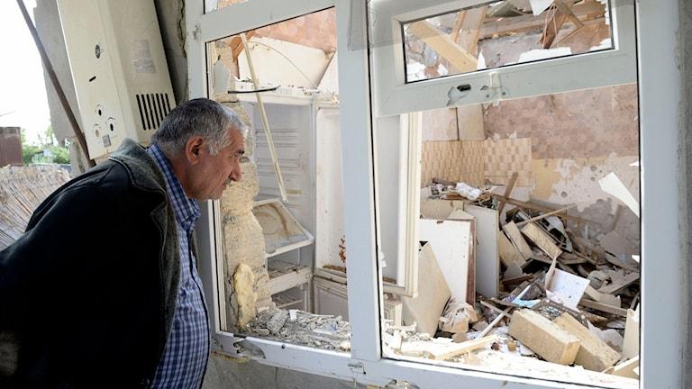 En man tittar ut genom ett fönster på förödelse efter granateld i området Nagorno-Karabach.