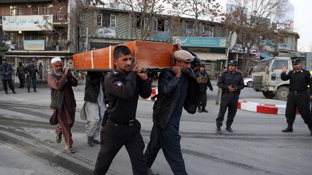 Fyra män bär en kista med en man i som dog i självmordsattacken på lördagen.
