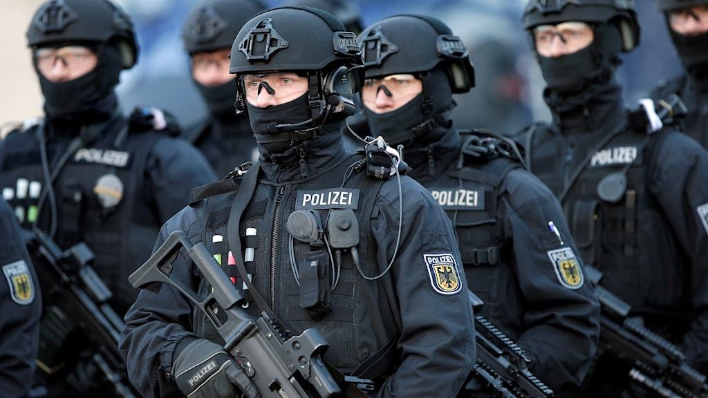 Närbild på Tyska poliser med skyddsdräkt och k-pist