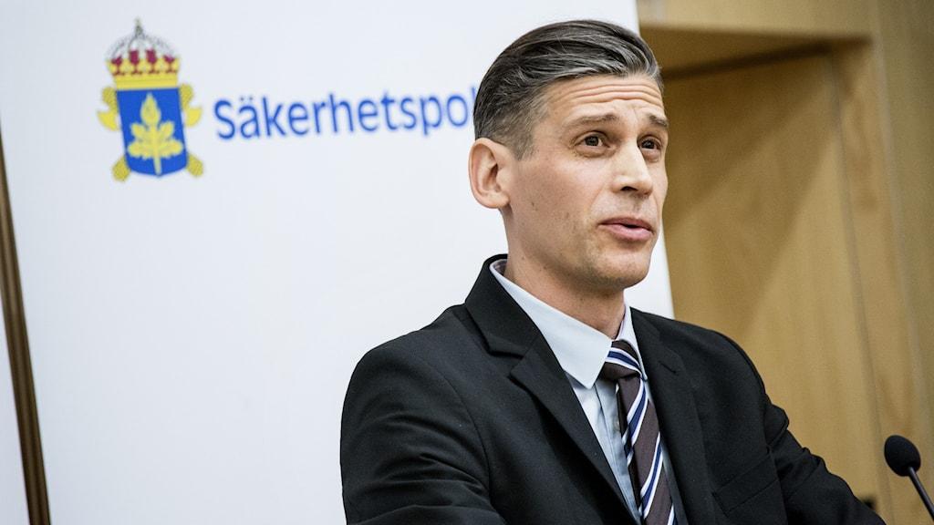 Daniel Stenling, enhetschef för Kontraspionage, framför en logga där det står Säkerhetspolisen