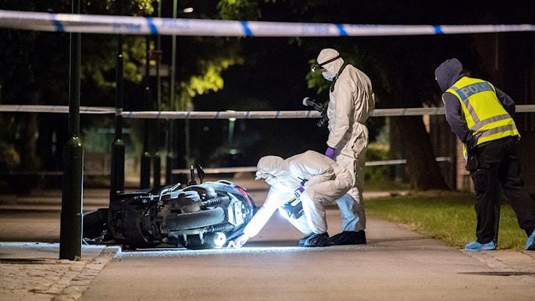 Polisens kriminaltekniker undersöker en moped på en gångbana vid Lindängsplan i Malmö efter att en man skjutits under torsdagskvällen.