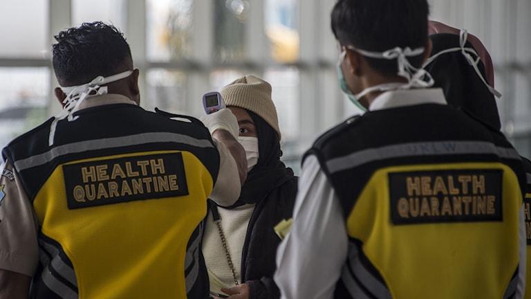 Sjukvårdspersonal tar tempen på resenärer vid Jakartas flygplats.
